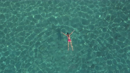 žába : AERIAL: Attractive young Caucasian woman in bikini swimming under surface in beautiful turquoise ocean. Sun rays penetrating sparkling transparent water revealing stunning rocky and sandy sea bottom
