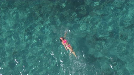 AERIAL: Attractive young Caucasian woman in pink bikini swimming backstroke in beautiful turquoise ocean. Sun rays penetrating sparkling transparent water revealing stunning rocky and sandy sea bottom Wideo