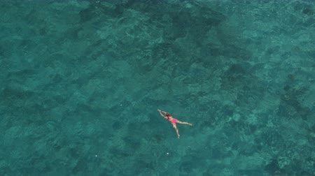 AERIAL, DISTANCING: Attractive young Caucasian woman swimming in deep beautiful turquoise ocean. Sunshine penetrating sparkling transparent water revealing stunning rocky and sandy sea bottom