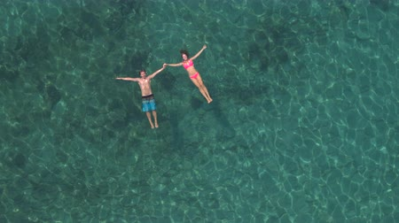 AERIAL, DISTANCING: Happy and loving girlfriend and boyfriend holding hands, relaxing and floating on water surface in amazing crystal clear ocean lagoon with visible rocks and stones on the seabed Wideo