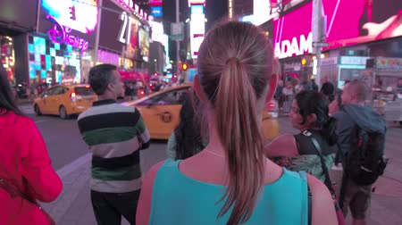 Бродвей : NEW YORK, USA - SEPTEMBER 28: HYPERLAPSE. Young woman walking on crowded busy Broadway st on iconic Times Square full of tourists sightseeing. Aggressive advertising with flashing images and neon signs