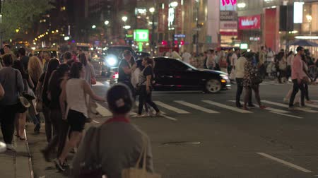 crossing road : NEW YORK, USA - SEPTEMBER 28: People of different ethnicities during evening rush hour walking on pedestrian crossing at big intersection on busy illuminated by neon signs New York streets at night.