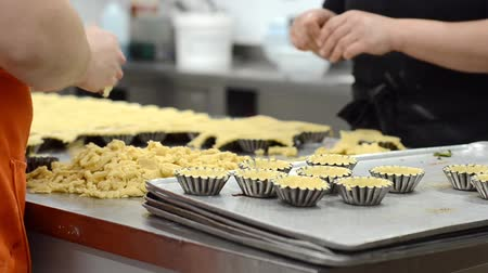 Pastry chef making tartlets, putting the dough in baking dishes, at kitchen of pastry shop.