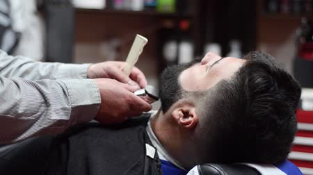 bigode : Barber shaving the beard of a handsome bearded man with an electric razor at the barber shop. Stock Footage