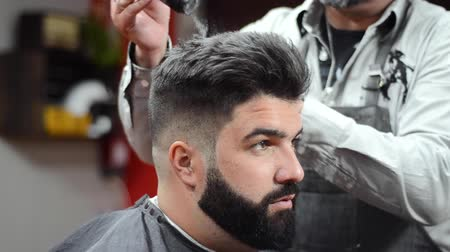 Barber using hair spray fixating hairdo at barber shop.