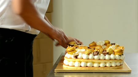 Confectioner decorating delicious cream cake with golden sweets. Dostupné videozáznamy