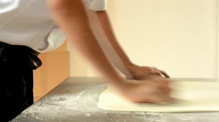 padeiro : Confectioner using rolling pin preparing fondant for cake decorating.