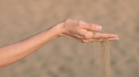 Slow motion of Woman hand pouring sand through fingers at the beach..