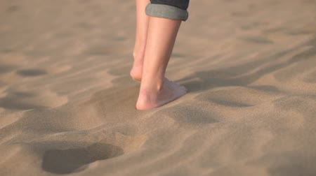 Close up, Slow motion. Woman feets walking on golden sand at the beach.