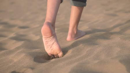 ślady stóp : Close up, Slow motion. Woman feets walking on golden sand at the beach.