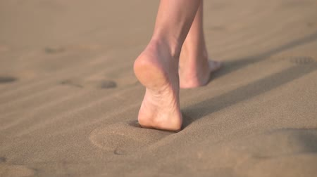 boso : Close up, Slow motion. Woman feets walking on golden sand at the beach.