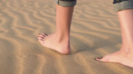 Close up, woman feets walking on golden sand at the beach.