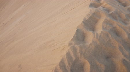 Walking on the edge of a sand dune in desertic landscape.