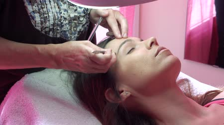 стегать : Young woman havind professional eyebrow correction at spa salon. Стоковые видеозаписи