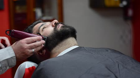Barber shaving the beard of a handsome bearded man with an electric razor at the barber shop. Dostupné videozáznamy