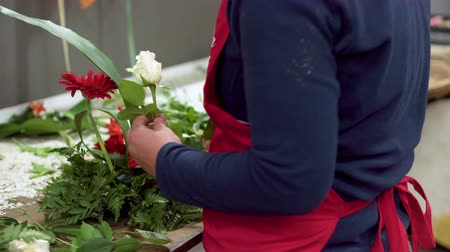 Close up of of woman florist creating bouquet of flowers .