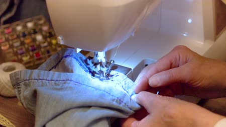 trousers : Sewing denim jeans. Repair jeans by sewing machine. Slow motion clip.