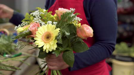 készítő : Close up of of woman florist creating bouquet of flowers .