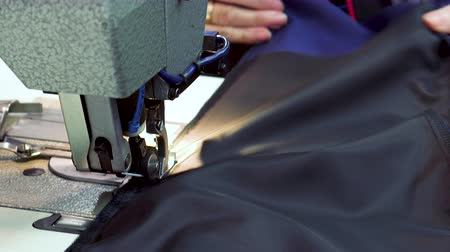 stockings : Workplace seamstress at the garment factory. A modern sewing machine in operation. Sewing a lining for a jacket. Stock Footage