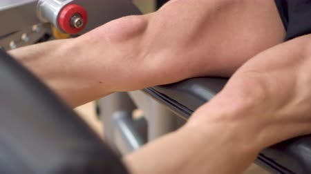 stehno : Close-up view of the man athlete with muscular legs working out at the gym leg curl trainer. 4k footage.
