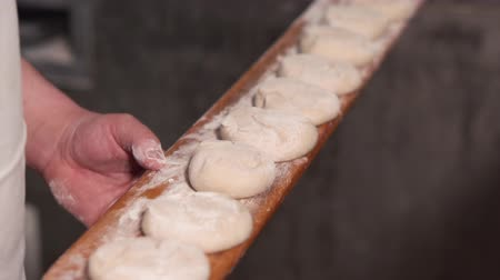 baker : The baker puts the dough in the oven. Slow motion. Close up.
