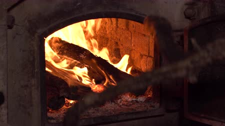 grzejnik : Loading wood to a rustic wood oven. Burning Fire In The Fireplace. 4k clip.