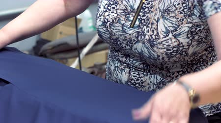 biust : Close-up: A seamstress woman steams a jacket using an old-fashioned iron. A womans hand holds the iron and smoothes the jacket, the steam from the iron.