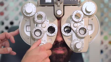 examinar : Close up shot of optometrist in white coat changing lenses on phoropter instrument and talking to male patient having eye exam.