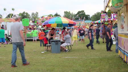 engedmény : People Walking around having fun at the carnival with camera panning Stock mozgókép