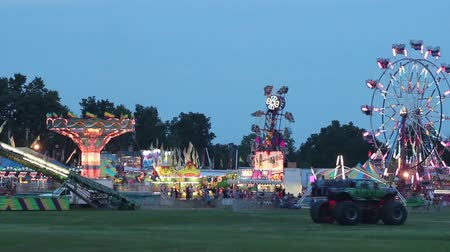 perili : The Carnival at Night Lit Up seeing the Zipper, Swings, and Scrambler rides Stok Video
