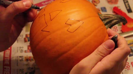 Man Drawing on Pumpkin Face