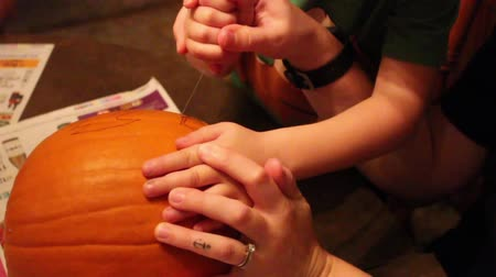 Helping Boy Carve Pumpkin Eye
