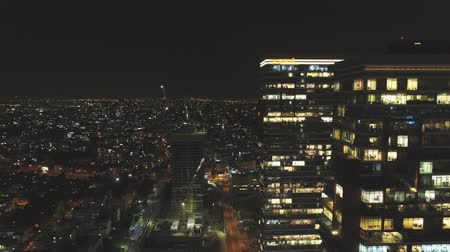 alkony : Aerial drone shot over metropolitan cityscape and skyscraper at night.