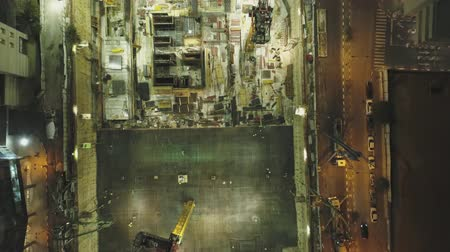 developing : Night scene at Construction site. Aerial drone above huge Constructions with cranes and heavy machines with cityscape in background Stock Footage