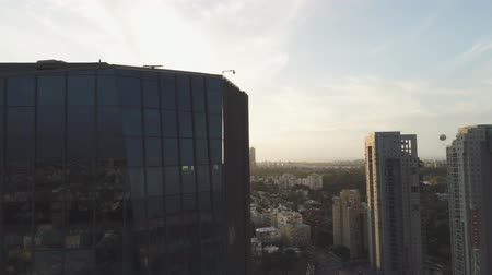 tükrözött : Tel aviv skyline at Daytime. reveal shot of Horizon view of towers and buildings behind reflected building. Downtown landscape of modern city background Stock mozgókép