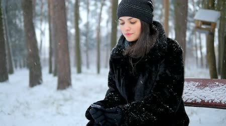 tél : A lonely girl is sitting on a bench in a winter park and waiting for a phone call. She is sad, she is a lonely girl.