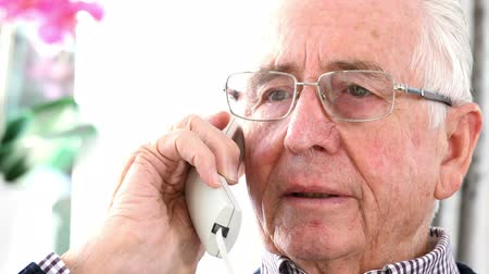 nuisance : Worried Senior Man Answering Telephone At Home