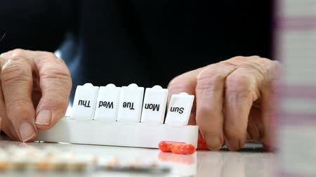 organizacja : Close Up Of Senior Man Organizing Medication Into Pill Dispenser