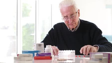 přihrádka : Senior Man Organizing Medication Into Pill Dispenser At Home Dostupné videozáznamy