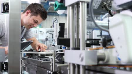 qualidade : Engineer With Digital Tablet Checking Automated Machine In Factory Stock Footage