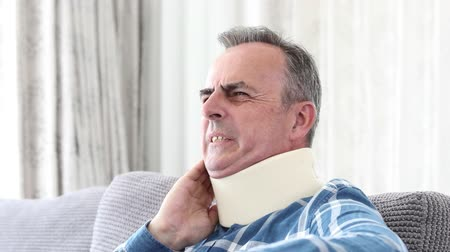 Mature Man Wearing Neck Brace Winces With Pain Stock Footage