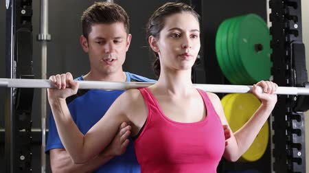 encouraging : Woman In Gym Lifting Weights On Bar Encouraged By Personal Trainer