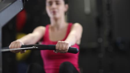veslování : Slow Motion Sequence Of Woman In Gym Exercising On Rowing Machine