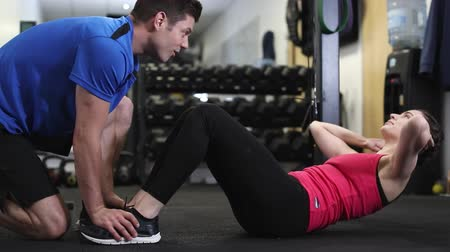 comprimento total : Woman In Gym Doing Sit Ups Encouraged By Personal Trainer Stock Footage