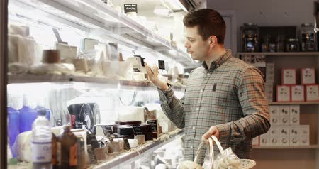 handheld shot : Male Customer In Delicatessen Shopping For Cheese