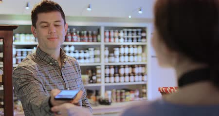 handheld shot : Male Customer Making Contactless Payment For Shopping Using Mobile Phone In Delicatessen Stock Footage
