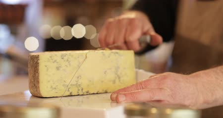 Close Up Of Male Sales Assistant En Delicatessen Cutting Slice Of Cheese Archivo de Video