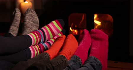 máma : Close Up Of Cosy Family At Home Wearing Socks Warming Feet By Flames Of Wood Burning Stove Fire