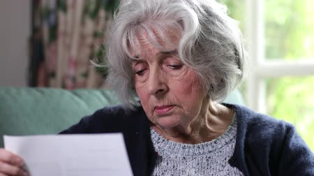 istek : Portrait Of Serious Senior Woman Reading Letter At Home Stok Video