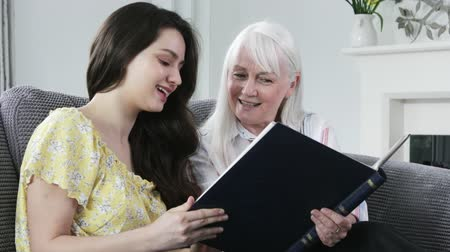 photo album : Mature Woman Looking At Photo Album With Adult Granddaughter Stock Footage